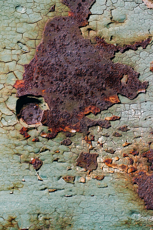 sheet of rusty metal with cracked and flaky paint, a metal surface with a bolt, abstract rusty metal texture with cracked green paint