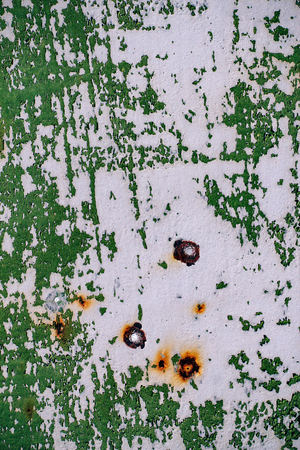 gray painted metal wall with cracked green paint, rust stains, sheet of rusty metal with cracked and flaky green paint , metal background for design with copy space Фото со стока