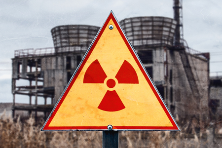 Sign of radiation hazard against radioactive waste on the building background, picture with a place for your text, copy space, your text here.