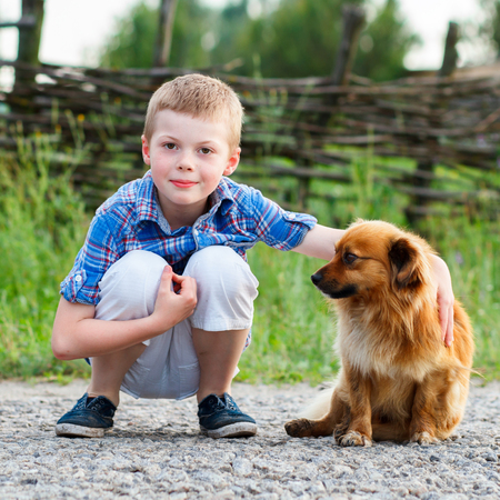 Child lovingly embraces his pet dog. Best friends. Outdoor Stockfoto