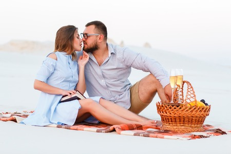 attractive couple sitting together on the white sand beach, young couple kissing on the beach, happy couple enjoying picnic on the beach , happy couple sitting on a blanket. Stock Photo