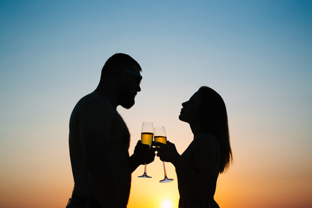 silhouettes of man and woman at sunset dramatic sky background, couple toasting wine glasses in romantic date setting, looking each other, smiling and holding in their hands glasses of champagne.