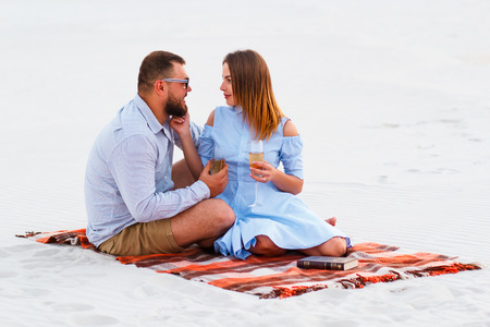 lovely attractive couple sitting together on the white sand beach, couple with wine or champagne during romantic dinner, young couple  holding glasses in hands, happy couple sitting on a blanket