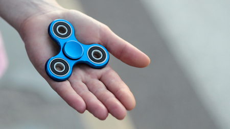 Blue metal popular fidget spinner toy on the palm of your hand, take it 写真素材