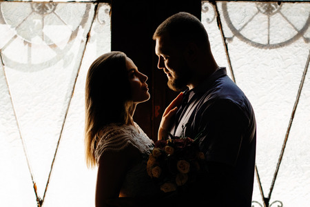 portrait of a romantic couple in a backlight from a window or door, silhouette of a couple in a doorway with a backlight, couple of lovers groom and bride at the window, girl holding flowers in hands Standard-Bild
