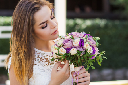 girl holding flowers in hands, young beautiful bride in white dress holding wedding bouquet, bouquet of bride from rose cream spray, rose bush, rose purple Memory Lane, violet eustoma, eucalyptus