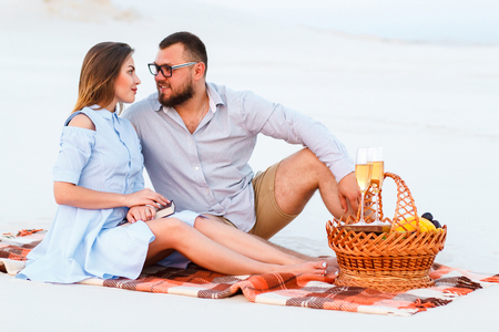 attractive couple sitting together on the white sand beach, looking each other, happy couple enjoying picnic on the beach and have good time on summer vacations, happy couple sitting on a blanket.