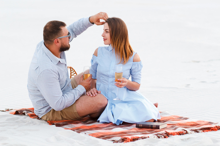 attractive couple sitting together, looking each other, happy couple enjoying picnic on the white sand beach and drinking wine or champagne during romantic dinner, happy couple sitting on a blanket.
