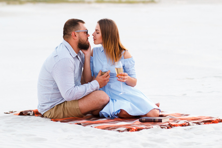 happy couple enjoying picnic on the white sand beach and drinking wine or champagne during romantic dinner, young couple kissing and holding glasses in hands, happy couple sitting on a blanket. Stock Photo