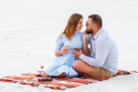 happy couple enjoying picnic on the white sand beach and drinking wine or champagne during romantic dinner, young couple kissing and holding glasses in hands, happy couple sitting on a blanket Stock Photo