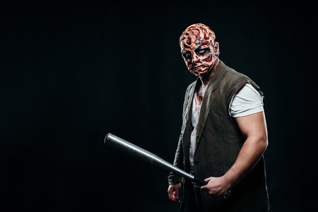 scary halloween theme and halloween makeup: scary man with a burnt face holds a baseball bat in his hands, serial maniac in a ragged suit, evil or angry superhero on a black background