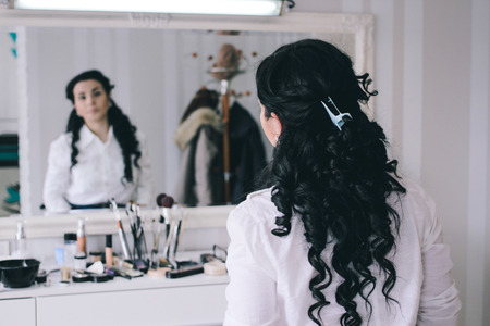 beauty salon, girl with long black hair sits at the mirror in the beauty studio,