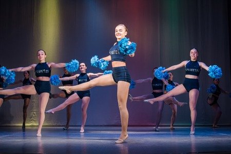athletes perform on stage, young cheerleaders perform at the cheerleading championship, girls are holding pompons, girls rotate on one leg, Pirouette