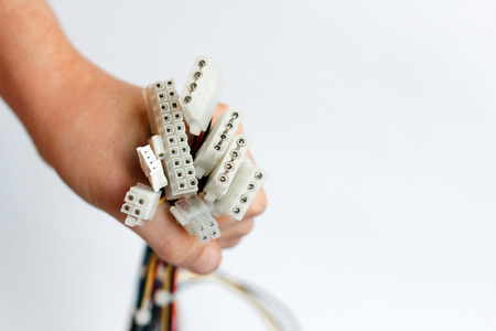 hand holds power cables from power supply unit on white background, PC motherboard power cables and connectors, 4pin peripheral connector, ATX 20+4 pin. Stockfoto