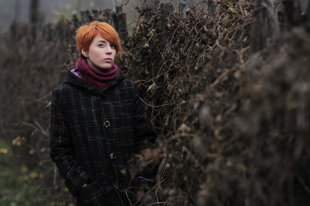sweet red-haired girl in a black coat and purple knitted scarf is standing by the fence overgrown with grapevine or ivy, girl or woman on a background of autumn or spring nature, overcast