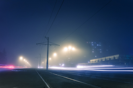 road with poles with high-voltage wires and tram tracks or tram rails , evening fog on the streets, poles with high-voltage wires, cityscape with freeze light or light painting