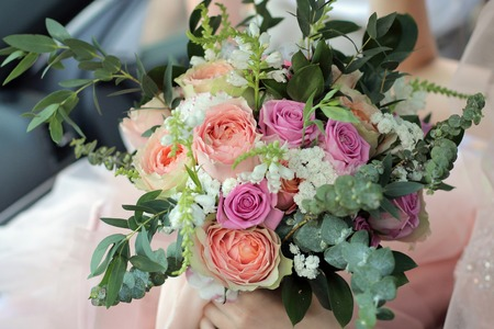 Bride holding a beautiful bridal bouquet. Wedding bouquet of peach roses by David Austin,  single-head pink rose aqua, eucalyptus, ruscus, gypsophila