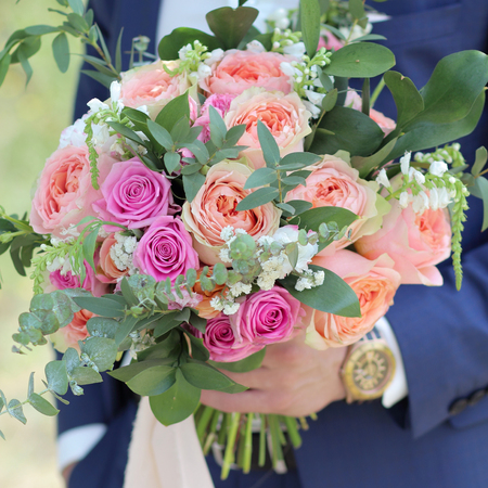 Groom holding a beautiful bridal bouquet. Wedding bouquet of peach roses by David Austin,  single-head pink rose aqua, eucalyptus, ruscus, gypsophila Imagens