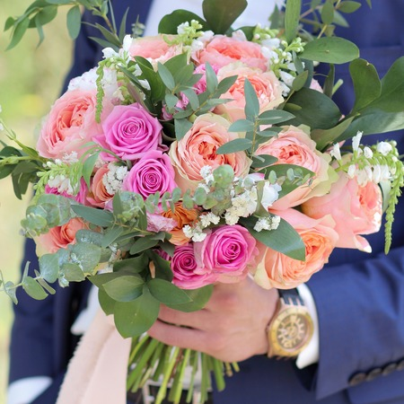 Beautiful bridal bouquet in hands of the groom. Wedding bouquet of peach roses by David Austin,  single-head pink rose aqua, eucalyptus, ruscus, gypsophila Imagens