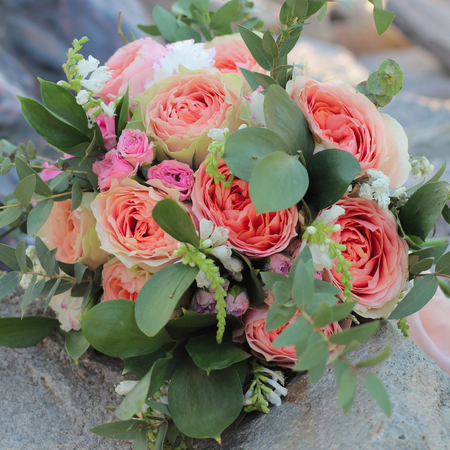 Bridal bouquet lying on the stones. Wedding bouquet of peach roses by David Austin,  single-head pink rose aqua, eucalyptus, ruscus, gypsophila Imagens