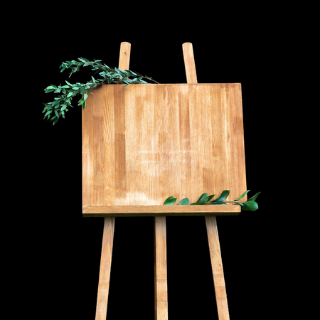 Copy space, your text here. Wooden easel with a board. Isolation on a black background Imagens