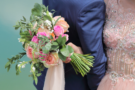 Beautiful bridal bouquet in hands of the bride. Wedding bouquet of peach roses by David Austin,  single-head pink rose aqua, eucalyptus, ruscus, gypsophila Imagens