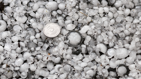 hail sized with a larger coin, hailstones on the ground after hailstorm, hail of great size Imagens