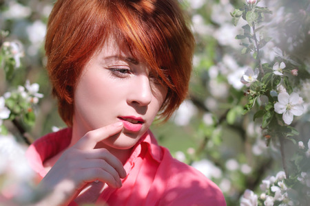 red-haired girl on a background of flowering trees, spring fashion girl outdoor portrait in blooming trees, beauty romantic woman in flowers