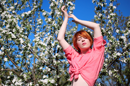 red-haired girl on a background of flowering trees, girl pulls her hands upwards, spring fashion girl outdoor portrait in blooming trees, beauty romantic woman in flowers