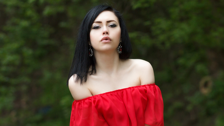 Portrait of a beautiful young girl with green eyes and bare shoulders, in a red dress on a green background summer nature. Imagens