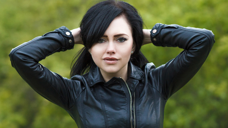 Portrait of a beautiful young girl in a leather jacket on the background of autumn nature.