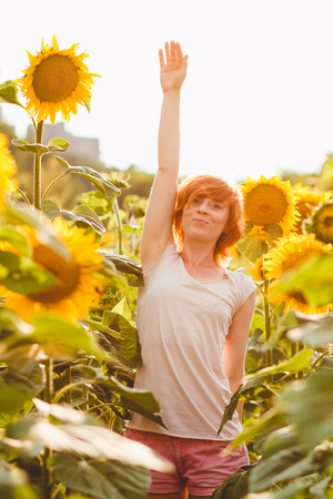 red-haired girl is standing next to a tall sunflower, a woman measures the height of a sunflower, her hand is lifted up Imagens