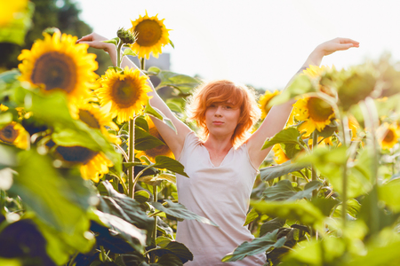 young girl enjoying nature on the field of sunflowers at sunset, portrait of the beautiful redheaded woman girl with a sunflowers in a sunny summer evening, hands raised up