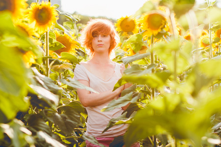 young girl enjoying nature on the field of sunflowers at sunset, portrait of the beautiful redheaded woman girl with a sunflowers in a sunny summer evening