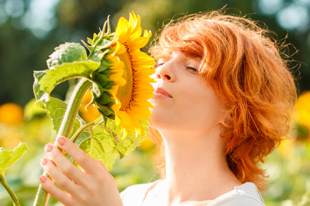 young red-haired girl admiring the sunflower, woman sniffing sunflower, girl enjoying nature on the field of sunflowers at sunset Imagens - 122194220