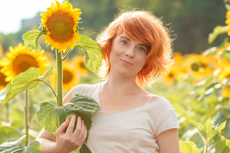red-haired girl hugging a tall sunflower at sunset, young redheaded woman in the field of sunflowers hugging a sunflower, funny situation