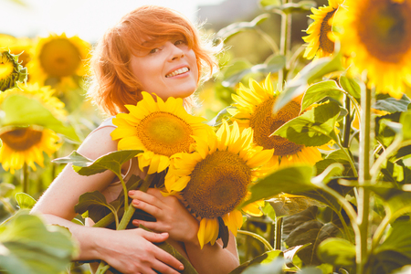 young redheaded woman in the field of sunflowers holding a huge bunch of flowers in a sunny summer evening Imagens - 122194221