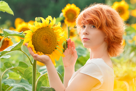 young girl enjoying nature on the field of sunflowers at sunset, portrait of the beautiful redheaded woman girl with a sunflowers in a sunny summer evening Imagens - 122194609
