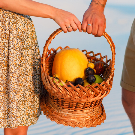 couple holding a wicker basket with fruit, man and woman having a picnic on the white sand beach or in the desert or in the sand dunes, guy and a girl with a basket in their hands