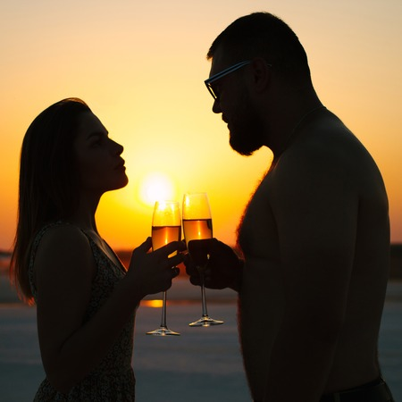 silhouette of a couple with glasses on sunset background, man and woman clanging wine glasses with champagne at sunset dramatic sky background