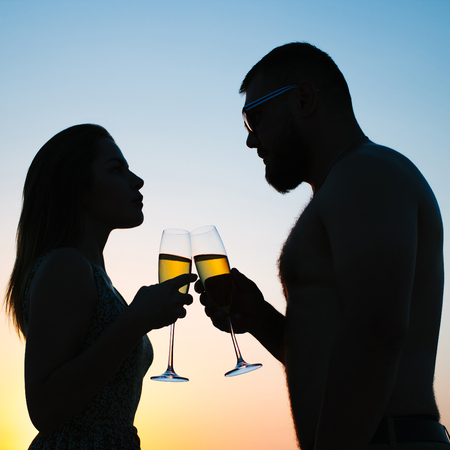 loving couple drinking wine or champagne during sunset time, silhouette of a couple with wineglasses on sunset background, man and woman, looking each other,  and holding in their hands glasses