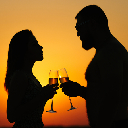 happy couple enjoying a glass of wine or champagne, silhouette of couple in love drinking wine from wineglasses during romantic dinner at sunset on the beach, sunset background