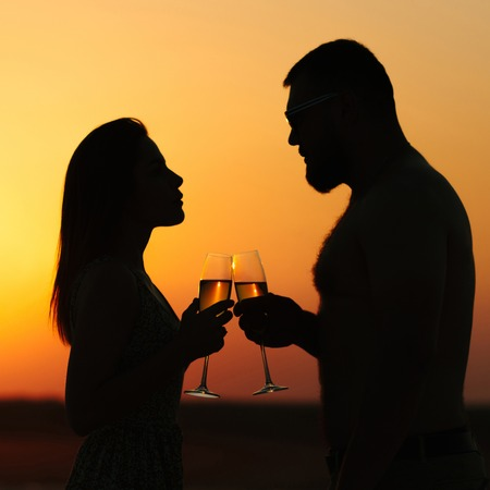 silhouettes of man and woman, happy couple in love on the beach at the sunset, looking each other, smiling and holding in their hands glasses of champagne