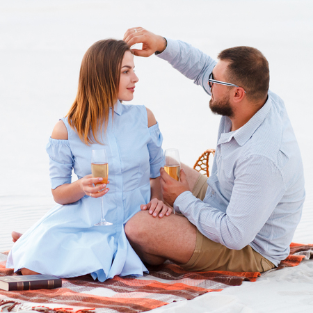 attractive couple sitting together, looking each other, happy couple enjoying picnic on the white sand beach and drinking wine or champagne during romantic dinner, happy couple sitting on a blanket