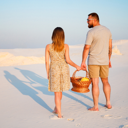 lovely attractive couple on the white sand beach or in the desert or in the sand dunes, guy and a girl with a basket in their hands, the couple left traces or footprints on the sand, rear view