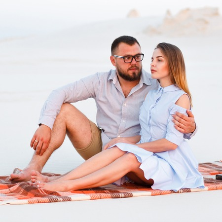 lovely attractive couple sitting together on the white sand beach, happy couple sitting on a blanket , happy couple enjoying picnic on the beach and have good time on summer vacations