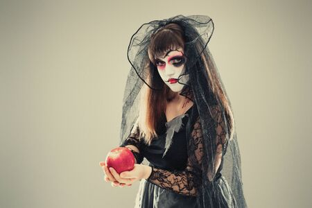 woman in a carnival costume of a witch or a dead bride holding an apple in her hands, gothic woman in witch costume on gray background, halloween portrait of girl with scary halloween makeup 스톡 콘텐츠