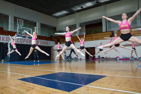 active pretty girls in action, group of cheerleaders jumping in the air demonstrate perfect stretching, hands raised up, girls in black and pink suit on the background of the gym, horizontal twine