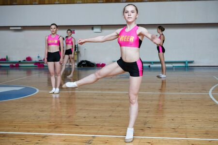 Dancers shows off their moves - pirouette, girls in black and pink sportswear train at the gym, sport young woman rotates on one leg, cheerleader dancer doing pirouette