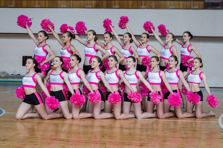 attractive young cheerleaders working out in sports club, group of cheerleaders with pom-poms in their hands, hands raised up, girls in black and pink suit with pompons on the background of the gym